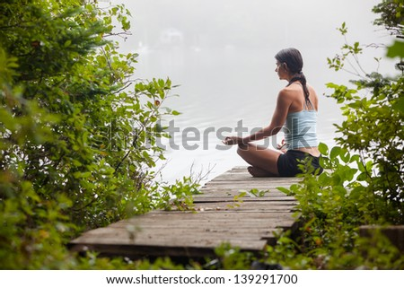 middle aged woman meditating on dock by a lake in the foggy morning, horizontal composition, Surry Maine - stock photo
