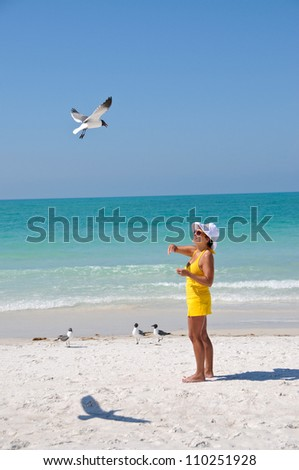 Middle Aged Woman on the Beach Feeding Seagulls - stock photo