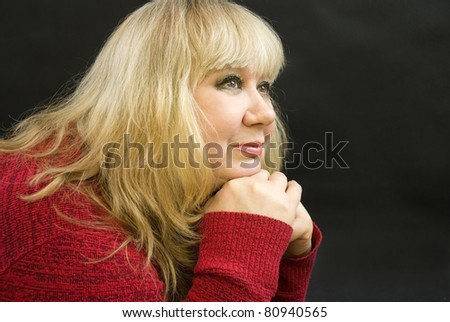 middle-aged woman posing on a black background - stock photo