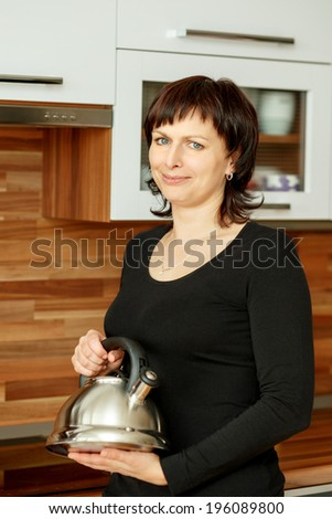 middle-aged woman preparing coffee in the kitchen with kettle - stock photo