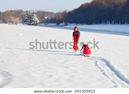 Middle aged woman pulling red sledge with her daughter across a snow field