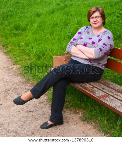 Middle-aged woman relaxing while sitting on a park bench - stock photo
