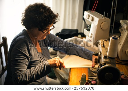 Middle aged woman sewing - stock photo