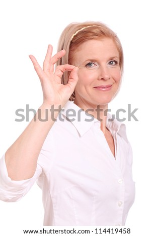 Middle aged woman showing ok sign over white background