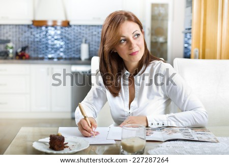 Middle aged woman sitting at dining table with recipe book, cake in plate in front of her and thinking about something nice - stock photo