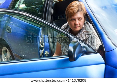 Middle-aged woman sitting in a blue car - stock photo