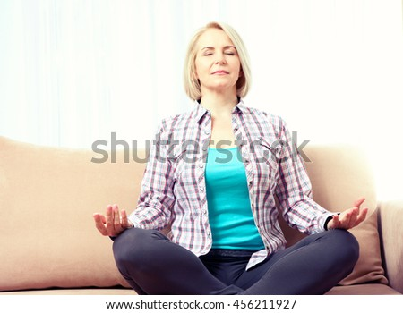 Middle-aged woman sitting relaxed in a pose lotus and meditating on the sofa in the living room. By toning applied photo
