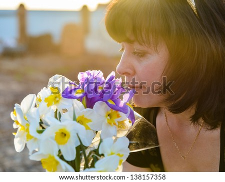middle-aged woman smelling a bouquet of flowers narcissus - stock photo