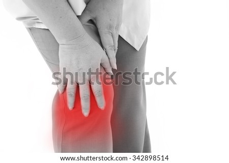 middle aged woman suffering from knee pain, joint injury or arthritis, hand holding knee - stock photo