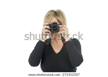 Middle aged woman taking a photograph with her camera against a white background