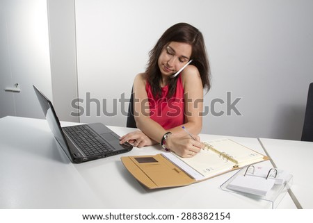Middle aged woman taking notes on the phone and working with computer