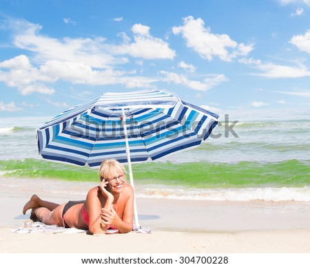 middle-aged woman talking on the phone at the beach - stock photo