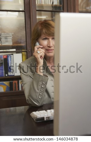 Middle aged woman using computer and cellphone in study room at home