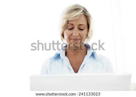 Middle-aged woman using computer. Close up with white background.