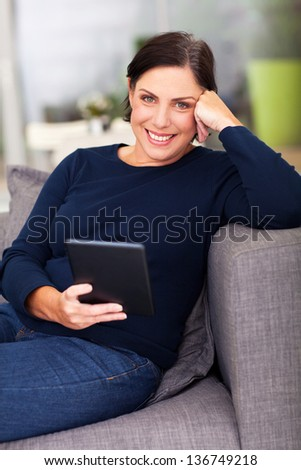 middle aged woman using tablet computer at home - stock photo