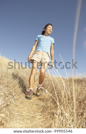 Middle-aged woman walking through tall grass