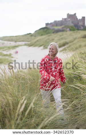 Middle Aged woman walking up the sand dune with a castle in the background. She is wearing warm casual clothing and smiling.  - stock photo