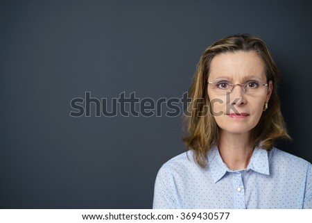 middle-aged woman wearing glasses looking at camera, with copy-space