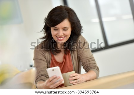 Middle-aged woman websurfing with smartphone