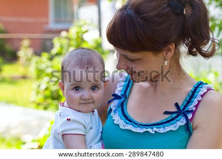 middle aged woman with a little girl in the garden - stock photo