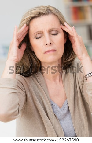 Middle-aged woman with a migraine headache sitting with her fingers to her temples and eyes closed in pain as she tries to relax - stock photo