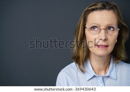 middle-aged woman with a pensive facial expression standing against grey background with copy-space