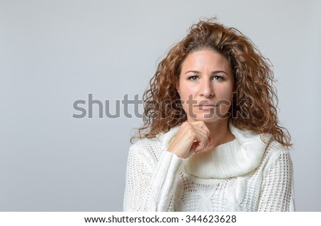 middle aged woman with a serious expression halding on hand to her chin - stock photo