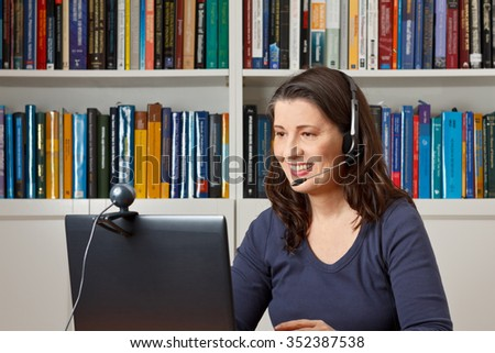Middle aged woman with computer, headset and webcam talking with friends via viewphone - stock photo