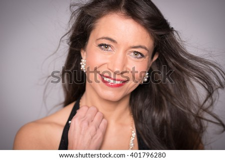 Middle aged woman with evening dress in front grey background - stock photo