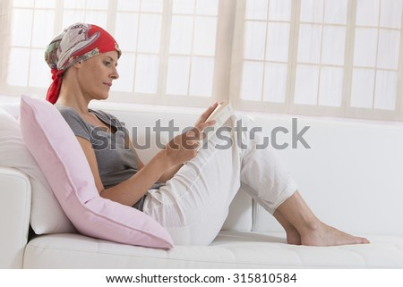 middle aged woman with headscarf is reading book on sofa at home - stock photo