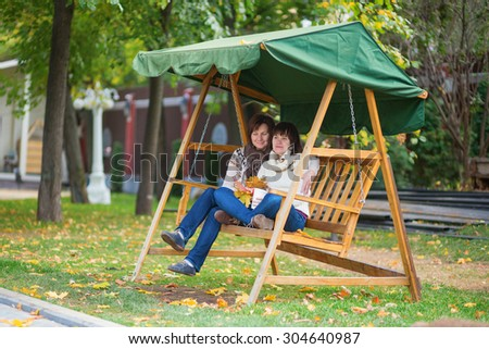 Middle aged woman with her adult daughter on a swing on a fall day, holding autumn leaves in their hands