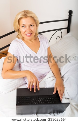 Middle-aged woman with laptop laying in her bed at home