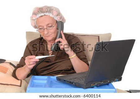 Middle aged woman with laptop on tray in bed, calling in sick.  Thermometer in left and phone in right hand