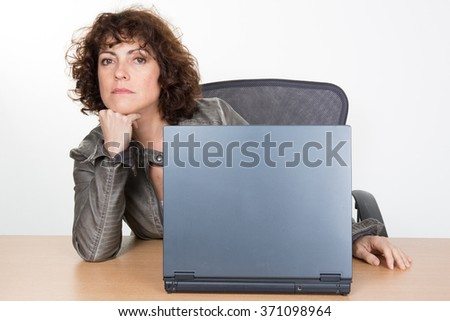 Middle-aged woman working at work on laptop - stock photo