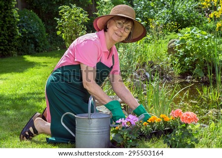 Middle-aged woman working in her garden kneeling on the lush green spring lawn transplanting potted flowers into a flowerbed turning to give the camera a friendly smile - stock photo