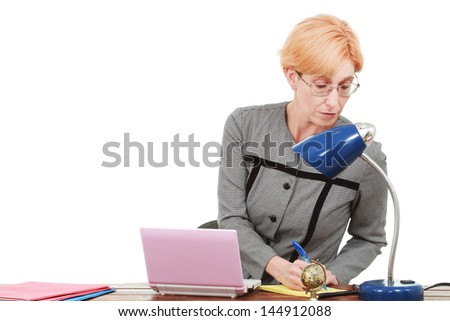 Middle aged woman works at her desk - stock photo