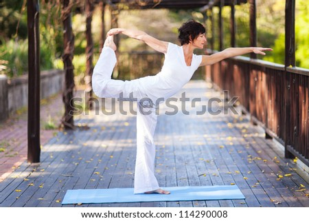 middle aged woman yoga pose outdoors - stock photo