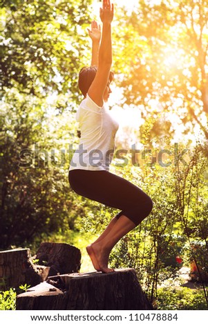 Middle aged women doing yoga  at the summer park - stock photo