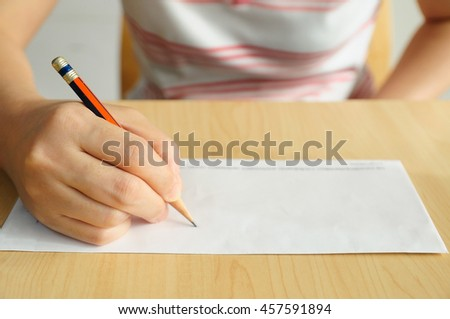 Middle Asian woman writing on envelope by left hand