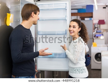 Middle class european family couple choosing new refrigerator in hypermarket