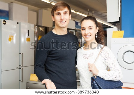 Middle class family couple selecting new domestic appliances at store - stock photo