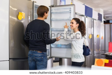 Middle class russian family couple choosing new refrigerator in hypermarket