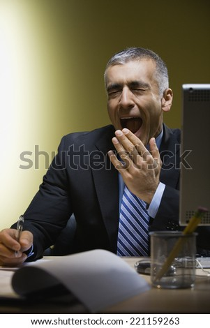 Middle Eastern businessman yawning at desk
