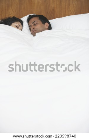 Middle Eastern couple sleeping in bed - stock photo