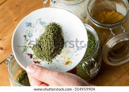 Middle Eastern cuisine: chef mixing spices and herbs to give flavour to the food. On the plate is dried parsley. - stock photo