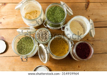 Middle Eastern cuisine: jars of spices and dried herbs ready to be used. Powdered ginger and garllic, cumin, dried parsley and mint, sumac and sunflower seeds. - stock photo
