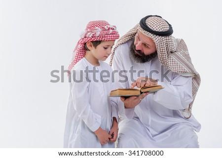 Middle eastern education, father teaching to read Koran. - stock photo