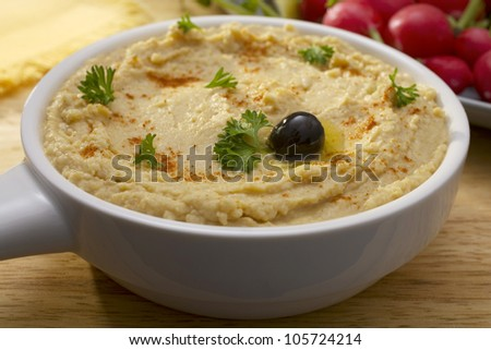 Middle Eastern hummus, sprinkled with paprika and parsley, drizzled with olive oil and topped with one black olive. - stock photo