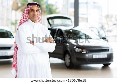 middle eastern male car dealer principal inside showroom - stock photo