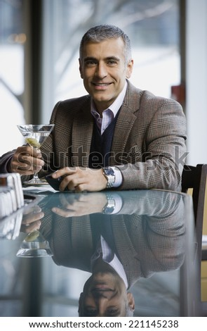 Middle Eastern man holding cocktail - stock photo
